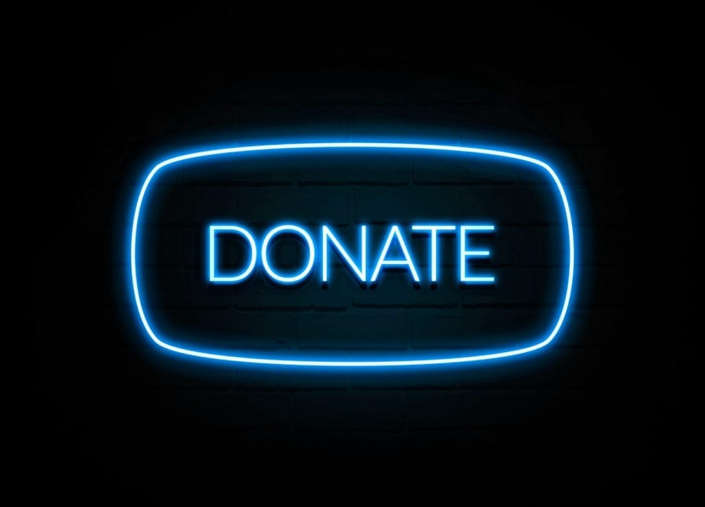 Donate  - colorful Neon Sign on brickwall